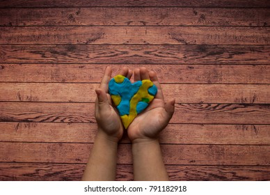 World Down syndrome day with blue yellow awareness heart holding by a child on wooden background with text space.