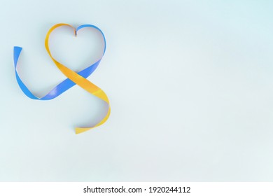 World Down Syndrome Day symbol. Yellow and blue ribbon on blue background with copy space. 21 March.