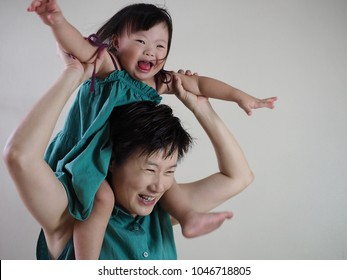 World Down Syndrome Day theme the joyous moment of little girl with Down syndrome riding lively on her mother's neck. Love does not count chromosomes or Mother's Day concept.