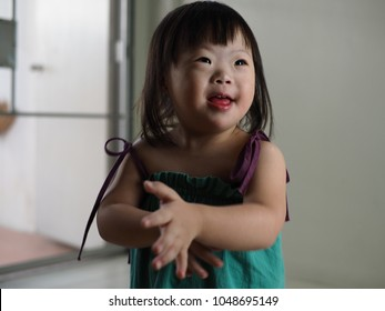 World Down Syndrome Day theme cheerful cute little girl with down syndrome smiling at her father and mother. Love does not count chromosomes concept.