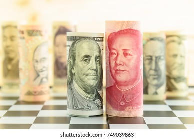 World economy and forex / foreign currency exchange concept : Rolled up scroll of USD US dollar and CNY Chinese yuan banknotes with portrait of Benjamin Franklin and Mao Zedong on a square chessboard.