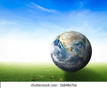World environment day concept: Earth global rest on green grass over blue sky background. Elements of this image furnished by NASA