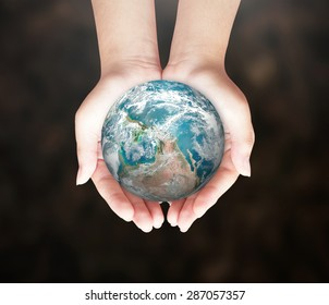 World environment day concept: Earth globe in human hands on blurred nature background. Elements of this image furnished by NASA