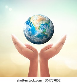 World environment day concept: Earth globe in human hands over blurred natured background. Elements of this image furnished by NASA