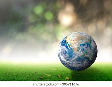 World environment day concept: Earth globe on green grass over blurred rainy with nature background. Elements of this image furnished by NASA
