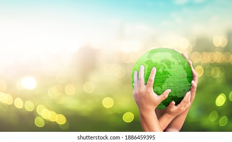 World environment day concept: Family hands holding earth global of grass over blurred green city background