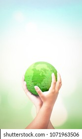 World environment day concept: Human hands holding earth globe of grass over blurred nature background