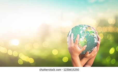 World environment day concept: Human hands holding earth global over blurred green city background. Elements of this image furnished by NASA