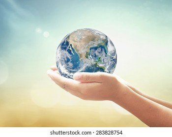 World environment day concept: Human hands holding earth globe over blurred abstract nature background. Elements of this image furnished by NASA