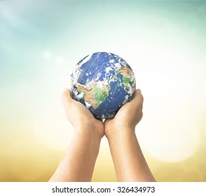 World environment day concept: Human hands holding earth global over blurred nature background. Elements of this image furnished by NASA