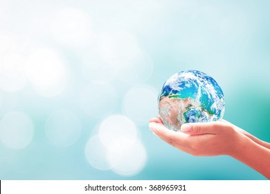 World environment day concept: Human hands holding earth global over blurred blue nature background. Elements of this image furnished by NASA