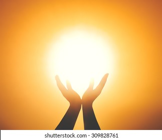 World environment day concept: Silhouette prayer hand blessing God on blurred candle light background