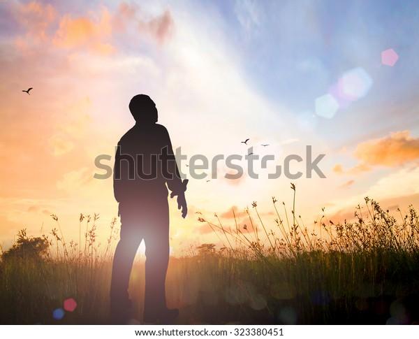 Konzept des Welttages: Silhouette des menschlichen Stehens, um Gott auf dem Wiese-Herbstsonnenuntergrund anzubeten