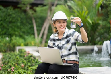 World environment day concept ,Thai Asian Female engineering working with a tablet laptop at sewage treatment plant, engineer controlling the quality of water , aerated activated sludge tank