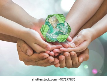 World environment day and ecology concept with family's hands saving green planet with recycle sign. Elements of this image furnished by NASA