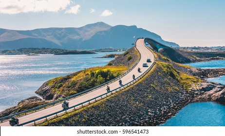 World famous Atlantic road bridge (Atlanterhavsvegen) with an amazing view over the norwegian mountains. Cars and bikes driving through an archipelago in Eide and Averøy in Møre og Romsdal, Norway.