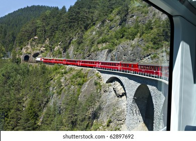 world famous swiss train Glacier Express makes it's way over a high viaduct into a tunnel, seen from inside the train