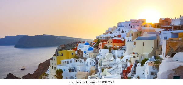 World famous traditional whitewashed chuches and houses of Oia village on Santorini island, Greece. Sunset.