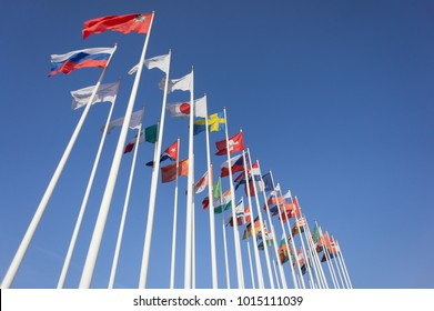 World Flags Blowing In The Wind On blue Sky Background. Flags of many nation.