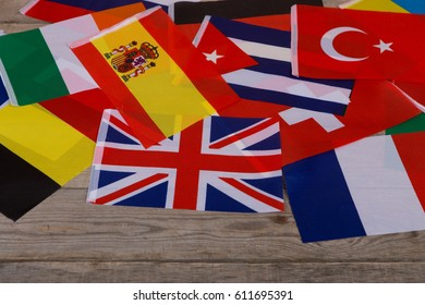 World flags, little flags of different countries on wooden table