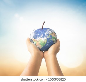World food day concept: Human hans holding apple fruit of earth globe on blurred nature background. Elements of this image furnished by NASA