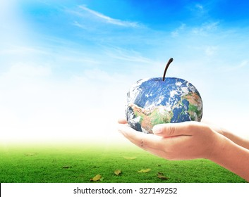 World food day concept: Human hands holding apple fruit of earth globe on green grass and blue sky background. Elements of this image furnished by NASA