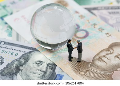 World or global financial tariff trade war negotiation talk, collaboration or discuss concept, miniature people businessman leader handshaking on Chinese yuan banknotes and US dollar.