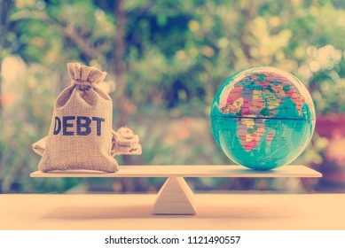 World or global / national debt crisis or imbalance concept : Debt bag, world globe on a balance scale, depicts the government's fiscal profligacy, excessive expenditure or increase public spending.