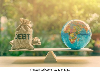 World or global / national debt crisis or imbalance concept : Debt bag and world globe on a balance scale, depicts the government's fiscal profligacy, excessive expenditure or increase public spending