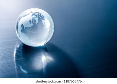 World globe crystal glass reflect on blue glossy table. Global business and economy. Environmental conservation or ecology concept