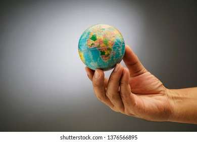 World globe on a palm over a grey background. Globalization Concept