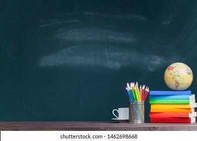 World globe on rainbow colored books in classroom. Back to school concept