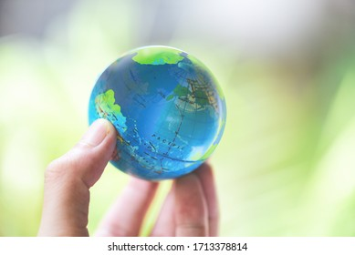 The world in the hand with nature background / hand holding globe environment green planet save the earth day concept