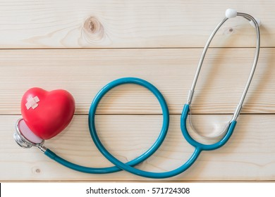 World health day campaign with red love heart  with cross bandage (band-aid) and medical doctor's stethoscope, first aid concept