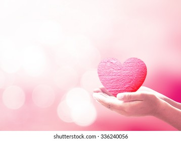 World health day concept: Human hands holding pink heart over blurred nature background