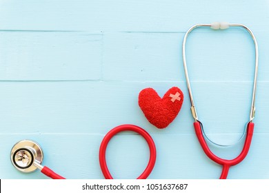 World health day, Healthcare and medical concept. Woman hand holding red heart with Stethoscope, notepad, thermometer and yellow Pill on Pastel white and blue wooden table background texture.