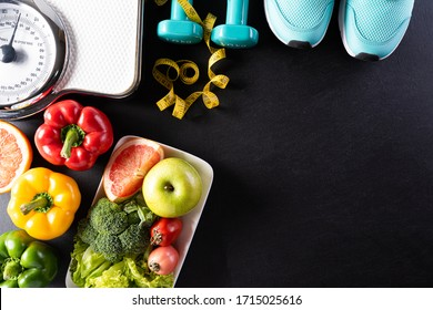 World health day, Healthcare and medical concept. Healthy food including fresh fruits, vegetables, weight scale, sports shoes, dumbells and measure tape on black background.