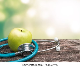 World health day and National Food Safety Education Month concept with healthy green natural nutrient apple fruit with antioxidant and doctor's stethoscope
