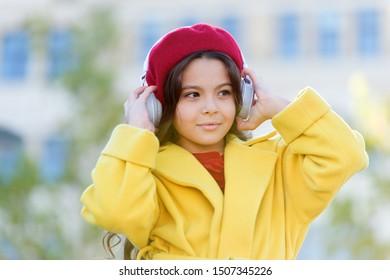 World of information. cheerful parisian girl in french beret. autumn fashion. school fall season. girl listen audio book. little girl in headset. online education. music lover. ebook technology.