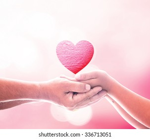 World kindness day concept: Father and son hands holding shape of heart symbol on blurred pink natural background