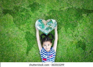 World kindness day, and international children day concept with happy kid raising heart planet on ecological friendly natural green lawn. Element of the image furnished by NASA