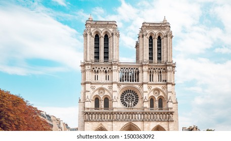 World known famous Notre Dame de Paris Cathedral with autumn foliage at the foreground