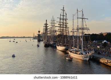 The world largest tall ships participating in race regatta are berthed by a quay of passenger terminal at the Daugava river in the port of Riga, Latvia. Masts decorated with marine flags. Sails down.