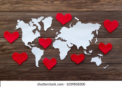 World map cutted from white paper and red felt hearts on the wooden background. Love and peace concept. Flat lay, top view, copy space, mock up, toned