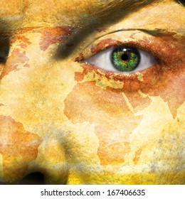 World map overlay on a man's face with a green eye