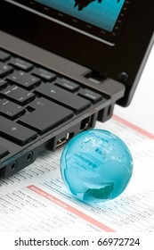 World markets analyze concept - laptop, glass globe and printed data sheet