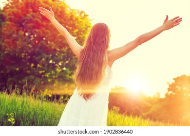 World mental health day concept: Silhouette of healthy woman raised hands at meadow background