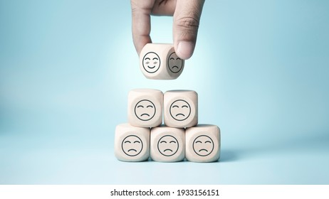 world mental health day concept or feedback rating and positive customer review, Businessman hand choose and turn sad face to smile face, wood cube stacking with sadness face icon on blue background