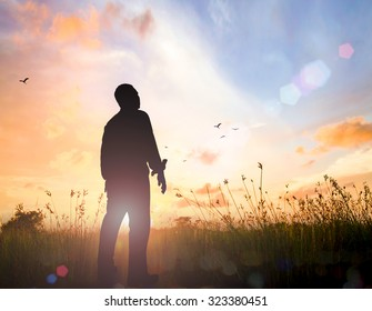 World mental health day concept: Silhouette of human standing to worship God in meadow autumn sunset background