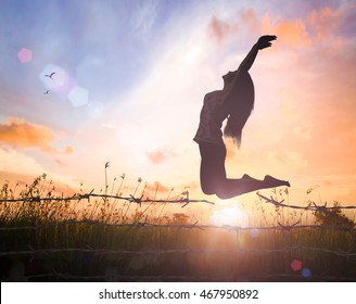 World mental health day concept: Silhouette of a girl jumping over broken barbed wire at meadow autumn sunset background
